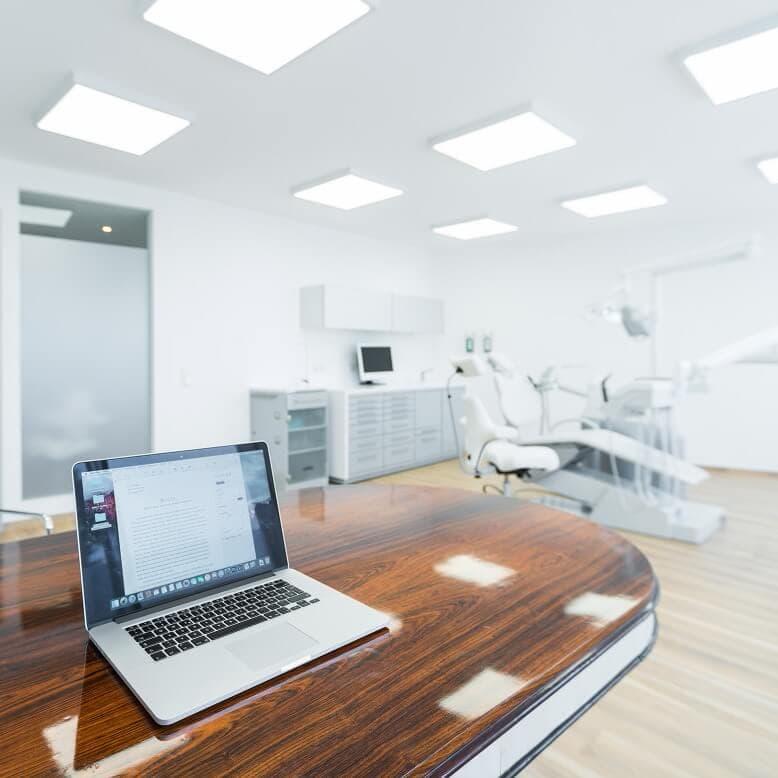 Praxis Rosenkranz Behandlungszimmer MacBook Zahnarztstuhl im Hintergrund